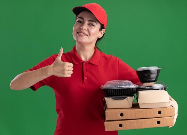 緑の壁に隔離された親指を示す紙の食品パッケージと食品容器が付いているピザのパッケージを保持している制服と帽子で笑顔の若い配達女性