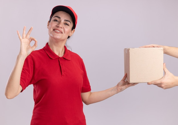 Smiling young delivery woman in uniform and cap giving cardbox to client doing ok sign