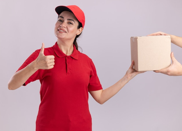 Smiling young delivery woman in uniform and cap giving cardbox to client showing thumb up