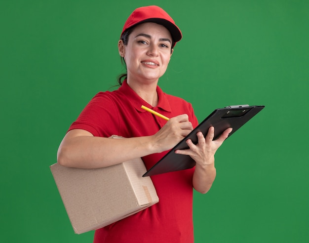Sorridente giovane donna delle consegne in uniforme e berretto con scatola di cartone e appunti con matita