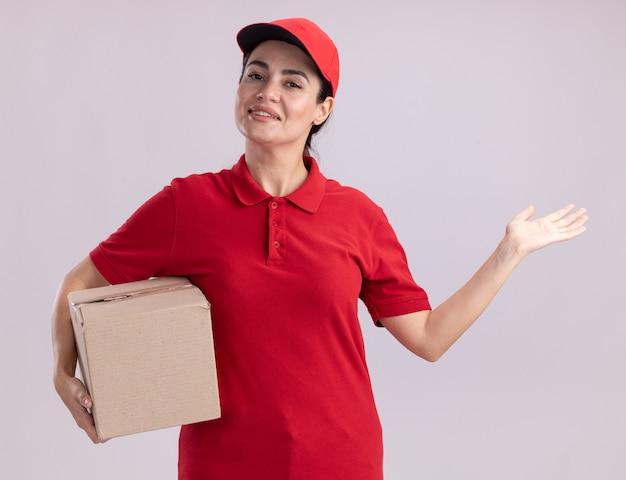 Sorridente giovane donna delle consegne in uniforme e cappuccio che tiene una scatola di cartone che mostra la mano vuota