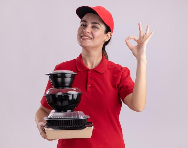 Sorridente giovane donna delle consegne in uniforme e berretto che tiene in mano un pacchetto di alimenti di carta e contenitori per alimenti che fanno segno ok