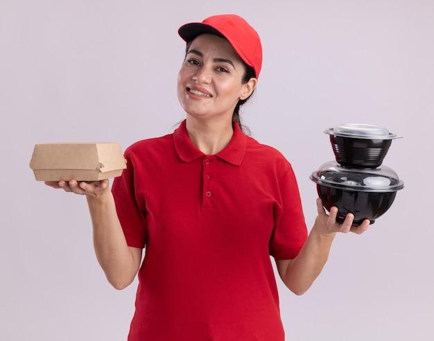 Sorridente giovane donna delle consegne in uniforme e berretto che tiene in mano un pacchetto di alimenti di carta e contenitori per alimenti isolati su parete bianca