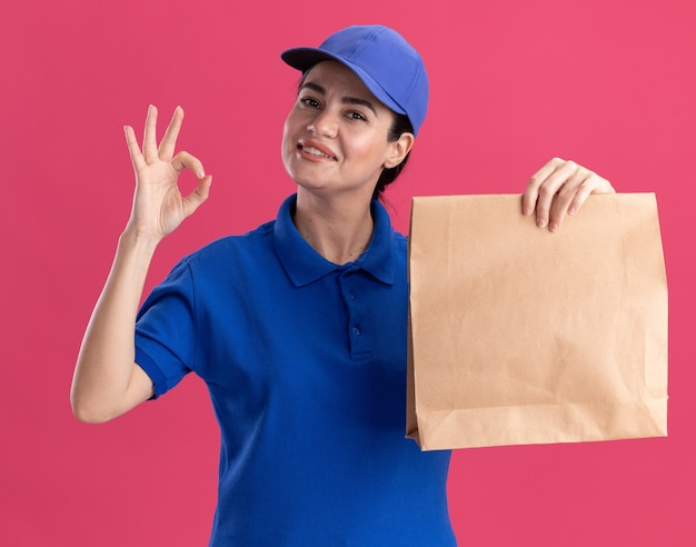 Sorridente giovane donna delle consegne in uniforme e berretto che tiene un pacchetto di carta facendo segno ok