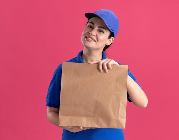 Sorridente giovane donna delle consegne in uniforme e cappuccio che tiene il pacchetto di carta guardando la parte anteriore isolata sulla parete rosa con spazio per la copia