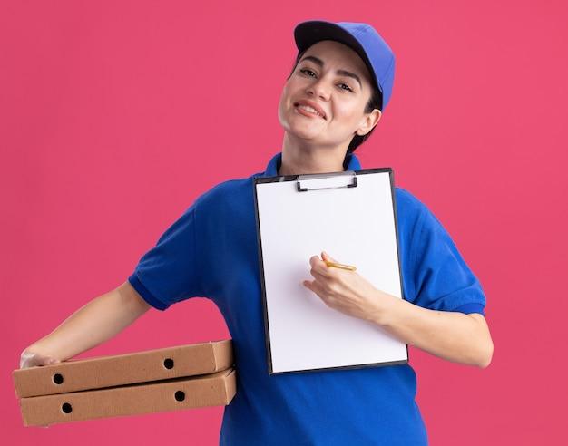 Sorridente giovane donna delle consegne in uniforme e berretto che tiene i pacchetti di pizza puntando la matita negli appunti