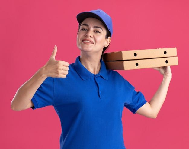 Sorridente giovane donna delle consegne in uniforme e berretto che tiene i pacchetti di pizza sulla spalla che mostra il pollice in su