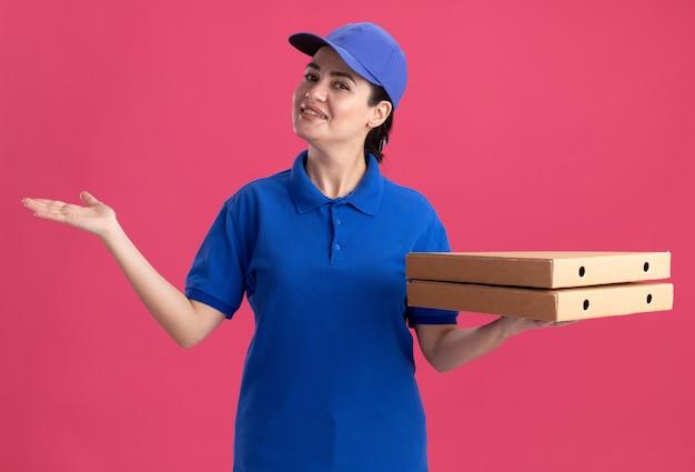 Sorridente giovane donna delle consegne in uniforme e berretto che tiene i pacchetti di pizza che mostrano la mano vuota