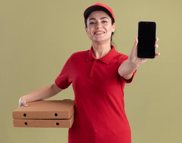 Sorridente giovane donna delle consegne in uniforme e berretto che tiene i pacchetti di pizza e allunga il telefono cellulare isolato sul muro verde oliva