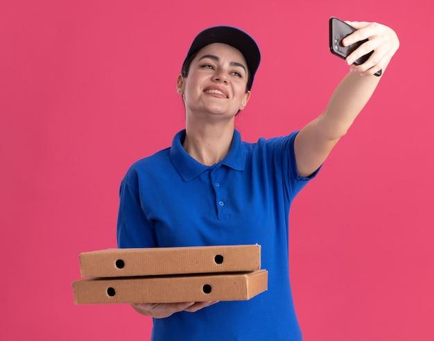 Sorridente giovane donna delle consegne in uniforme e berretto in possesso di pacchetti di pizza che prendono selfie