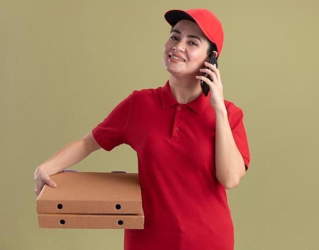 Sorridente giovane donna delle consegne in uniforme e berretto in possesso di pacchetti di pizza parlando al telefono