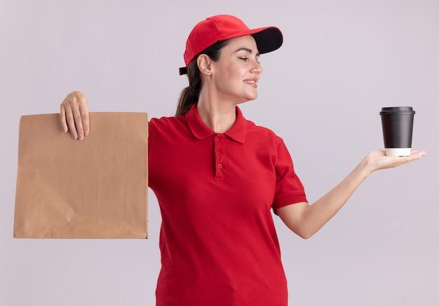 Sorridente giovane donna delle consegne in uniforme e cappuccio che tiene la tazza di caffè in plastica e il pacchetto di carta guardando la tazza di caffè isolata sul muro bianco