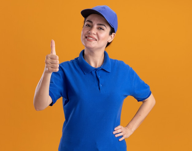 Smiling young delivery woman in uniform and cap keeping hand on waist showing thumb up