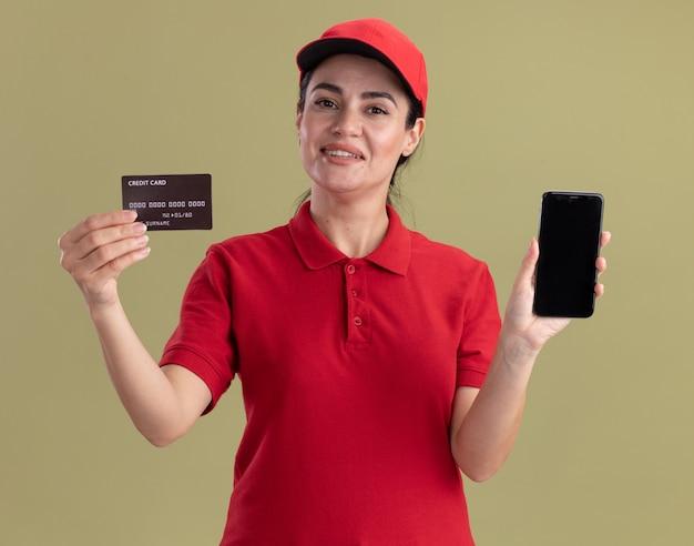 Sorridente giovane donna delle consegne in uniforme e berretto che mostra carta di credito e telefono cellulare isolato su parete verde oliva