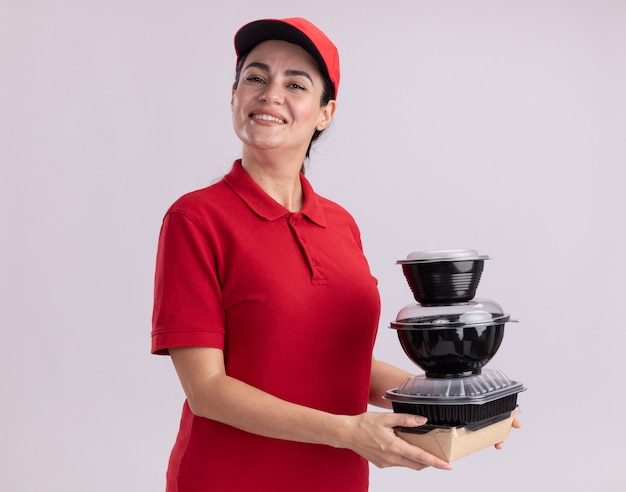 Smiling young delivery woman in uniform and cap standing in profile view holding paper food package and food containers