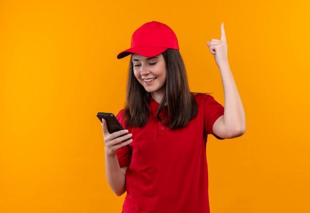 赤い帽子に赤いtシャツを着ている若い配達の女性の笑顔と指を上に孤立した黄色の壁