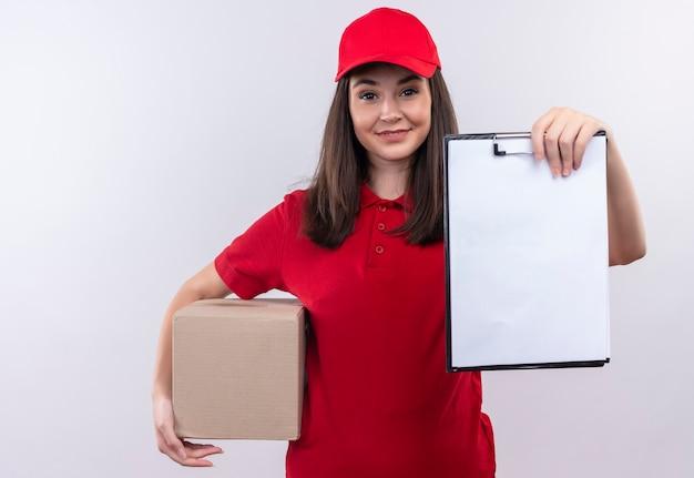 孤立した白い壁にボックスとクリップボードを保持している赤い帽子に赤いtシャツを着て笑顔の若い配達の女性