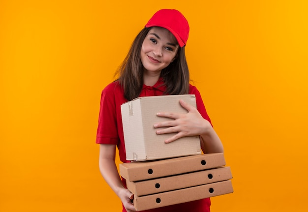 孤立したオレンジ色の壁にボックスとピザの箱を保持している赤い帽子に赤いtシャツを着ている若い配達女性の笑顔