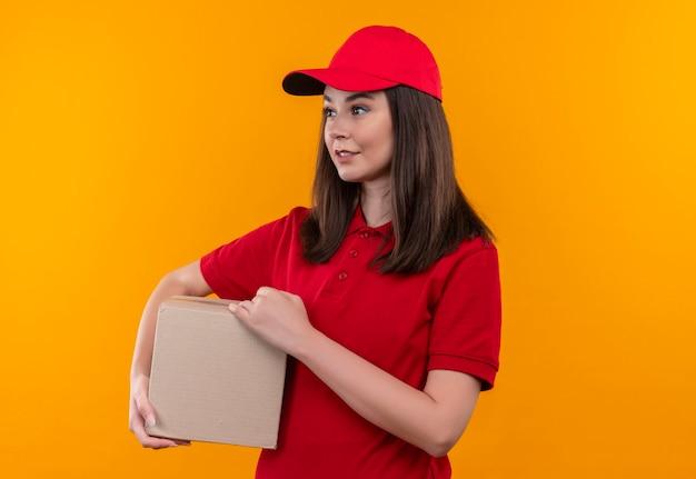 孤立したオレンジ色の壁にボックスを保持している赤い帽子の赤いtシャツを着て笑顔の若い配達の女性