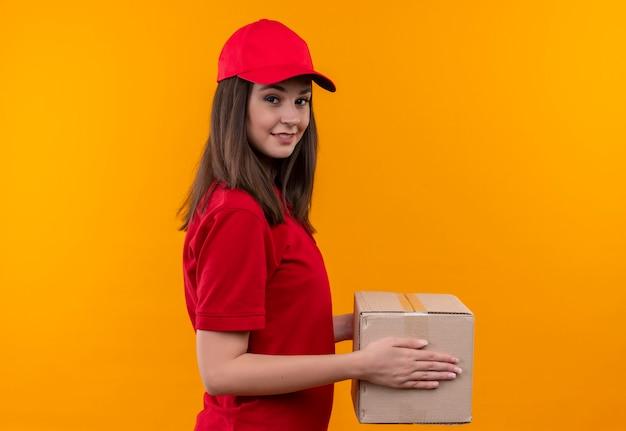 孤立した黄色の壁にボックスを保持している赤い帽子に赤いtシャツを着て笑顔の若い配達の女性