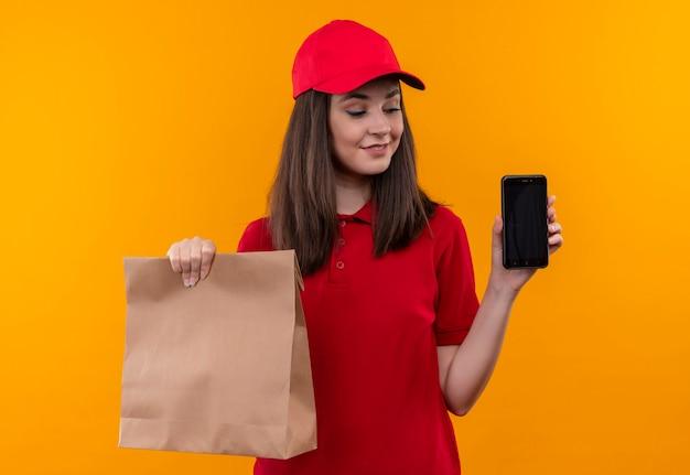 격리 된 노란색 벽에 패키지와 전화를 들고 빨간 모자에 빨간 티셔츠를 입고 웃는 젊은 배달 여자