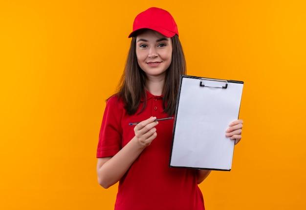 孤立したオレンジ色の壁にパンとクリップボードを保持している赤い帽子に赤いtシャツを着ている若い配達女性の笑顔