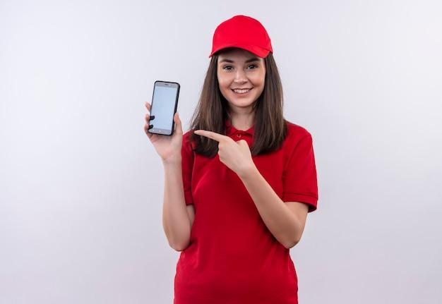 격리 된 흰 벽에 전화를 들고 빨간 모자에 빨간 티셔츠를 입고 웃는 젊은 배달 여자
