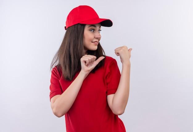 赤い帽子に赤いtシャツを着ている笑顔の若い配達女性が孤立した白い壁に戻るを指す