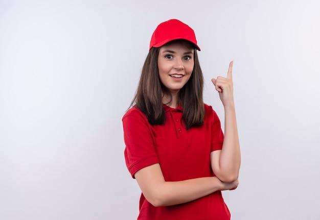 빨간 모자에 빨간 티셔츠를 입고 웃는 젊은 배달 여자가 격리 된 흰 벽에 위로를 가리 킵니다.