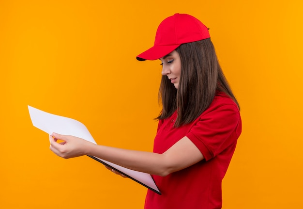 Smiling young delivery woman wearing red t-shirt in red cap flipping through a clipboard on isolated yellow wall