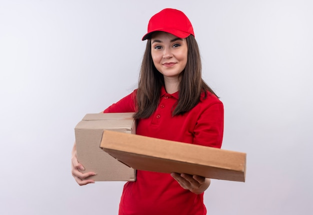 Smiling young delivery woman wearing red t-shirt in red cap holding a box and holds out the pizza box on isolated white wall
