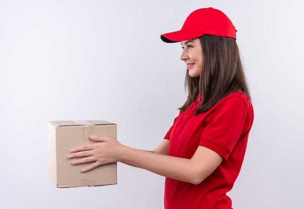 Sorridente giovane donna di consegna che indossa la maglietta rossa in berretto rosso che tiene una scatola sulla parete bianca isolata