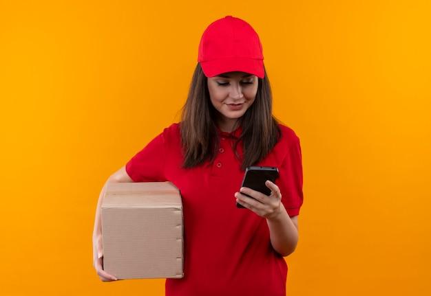 Sorridente giovane donna di consegna che indossa la maglietta rossa in berretto rosso che tiene una scatola e fa una chiamata sulla parete arancione isolata