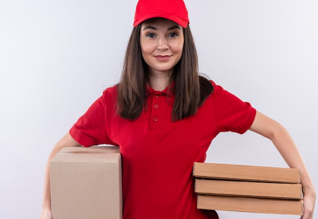 Smiling young delivery woman wearing red t-shirt in red cap holding a box and pizza box on isolated white wall