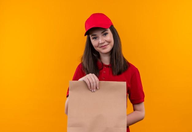 Sorridente giovane donna di consegna che indossa la maglietta rossa in berretto rosso che tiene un pacchetto sulla parete arancione isolata