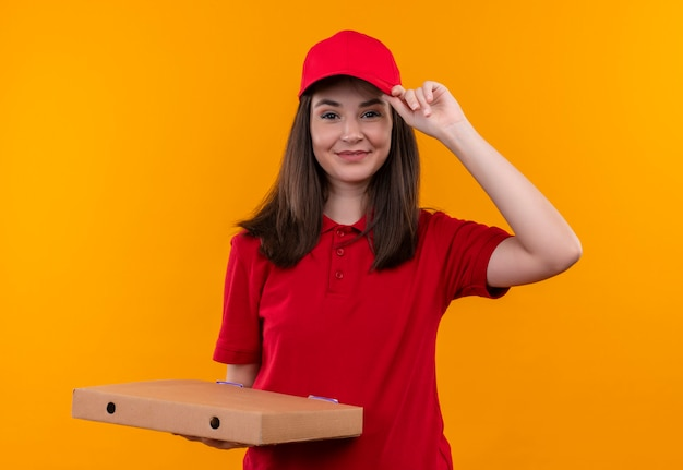 Sorridente giovane donna di consegna che indossa la maglietta rossa in berretto rosso che tiene una scatola di pizza sulla parete arancione isolata