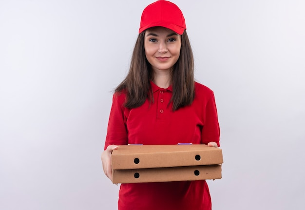 Smiling young delivery woman wearing red t-shirt in red cap holding a pizza box on isolated white wall