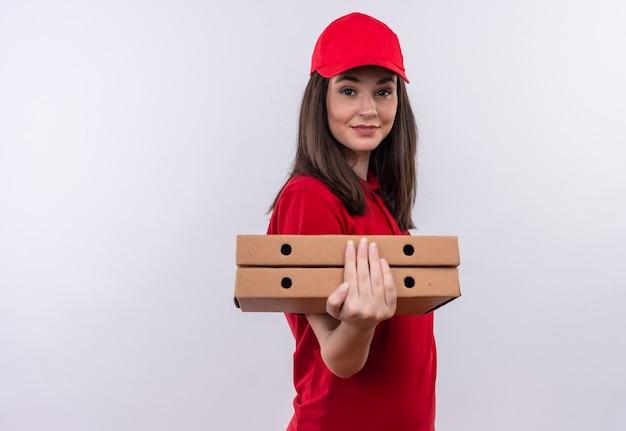 Sorridente giovane donna di consegna che indossa la maglietta rossa in berretto rosso che tiene una scatola di pizza sul muro bianco isolato