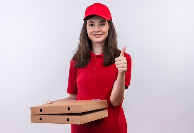 Smiling young delivery woman wearing red t-shirt in red cap holding a pizza box and showing thumbs up on isolated white wall