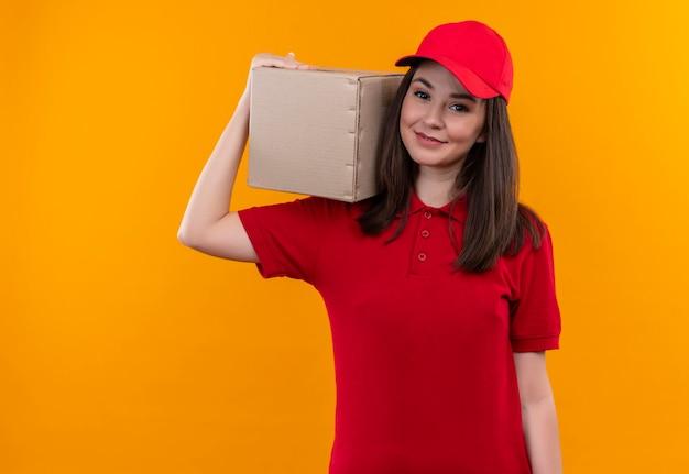 Sorridente giovane donna di consegna che indossa la maglietta rossa in berretto rosso sulla scatola di spalla sulla parete arancione isolata