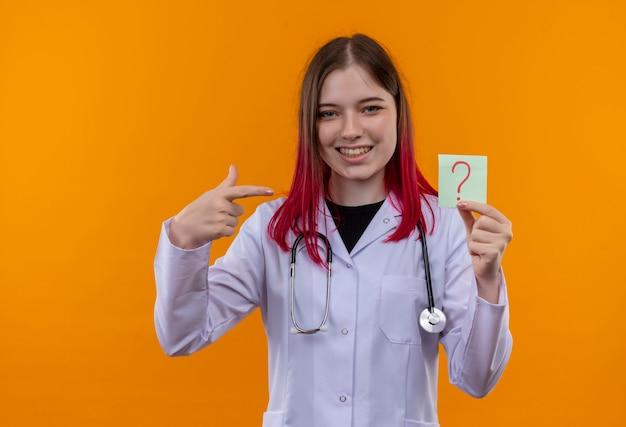 聴診器の医療ローブを身に着けている笑顔の若い医者の女の子は、孤立したオレンジ色の背景に彼女の手に紙の疑問符に指を指します