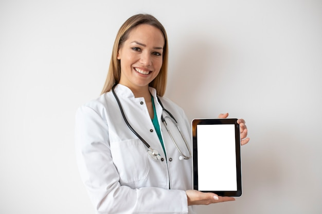 Smiling young doctor pointing at tablet isolated on white