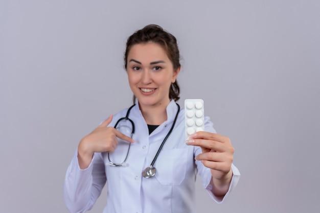 錠剤を保持し、白い壁に自分自身を指す聴診器を身に着けている医療用ガウンを身に着けている若い医師の笑顔