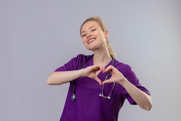 Il giovane medico sorridente che porta l'abito medico viola e lo stetoscopio mostra il gesto del cuore sulla parete bianca isolata