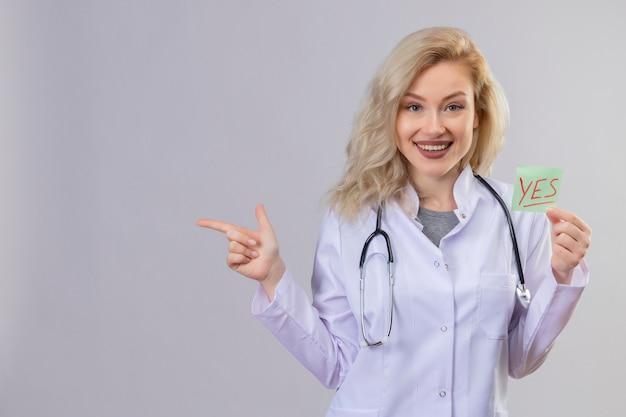 흰 벽에 종이 예 마크와 포인트를 들고 의료 가운에 청진기를 입고 웃는 젊은 의사