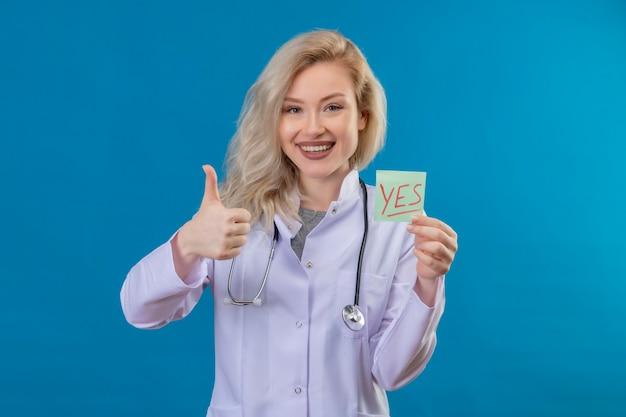 종이 들고 의료 가운에 청진기를 입고 웃는 젊은 의사 예 파란색 벽에 그녀의 엄지 손가락을 표시