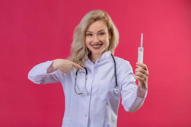 注射器を保持している医療用ガウンで聴診器を身に着けている若い医者の笑顔と赤い背景に自分自身を指しています
