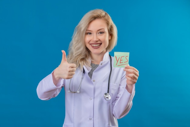 Smiling young doctor wearing stethoscope in medical gown holding paper yes mark her thumb up on blue wall
