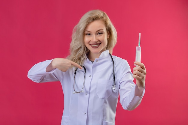 Smiling young doctor wearing stethoscope in medical gown holding syringe and points herself on red backgroung