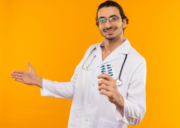 청진 기 들고 약을 들고 의료 가운을 입고 의료 안경 웃는 젊은 의사 복사 공간이 격리 된 노란색 벽에 손으로 손으로 포인트